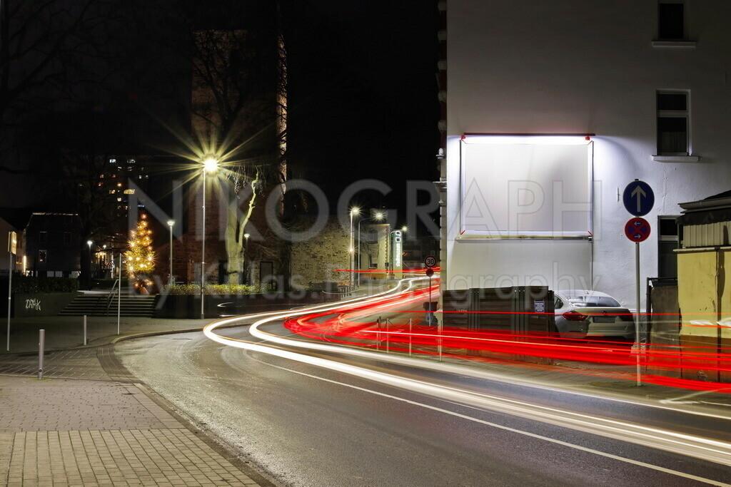 Aussenwerbung mit Lighttrails | Nachtaufnahme einer beleuchteten Plakattafel mit Lichtspuren vorbeifahrender Autos.