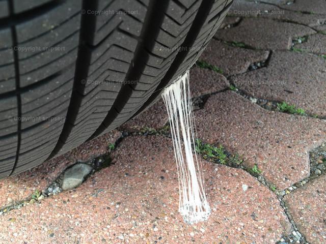 Klebender Kaugummi am Autoreifen | Detail von einem Autoreifen mit einem haftenden Kaugummi