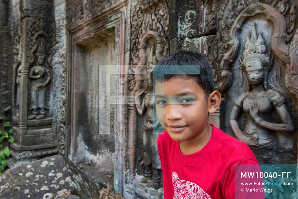 MW10040-FF   Kambodscha   Siem Reap   Reportage: Sombath erkundet Angkor   Porträt von Sombath. Hier besucht er Ta Prohm, den Dschungeltempel mit vielen Steinreliefs der Apsara-Tänzerinnen.  Der achtjährige Sombath lebt in Kambodscha im Dorf Anjan, sechs Kilometer westlich von Siem Reap entfernt. In seiner Freizeit nimmt ihn manchmal sein Onkel in die berühmte Tempelanlage von Angkor mit. Besonders mag er die riesigen Wurzeln der Kapokbäume, die auf den uralten Mauern wachsen. Seine Lieblingstempel in Angkor sind Ta Prohm, Banteay Kdei und Preah Khan.  ** Feindaten bitte anfragen bei Mario Weigt Photography, info@asia-stories.com **