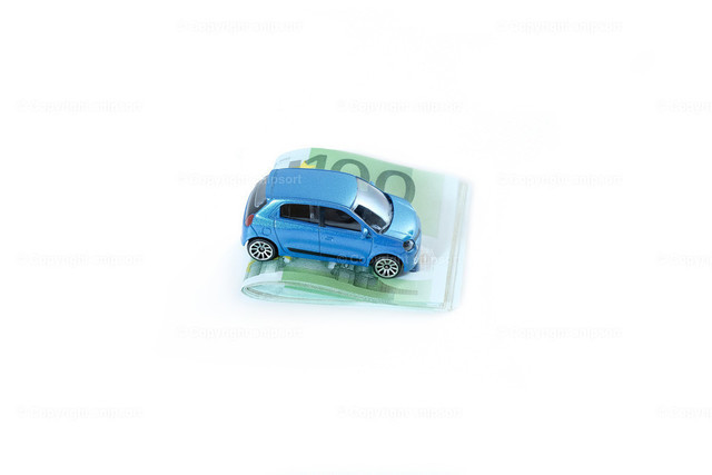 Blaues Auto auf Geldscheinen   Ein Modellauto auf einem Geldstapel aus 100-Euro-Banknoten zum Thema Konzept Autokosten