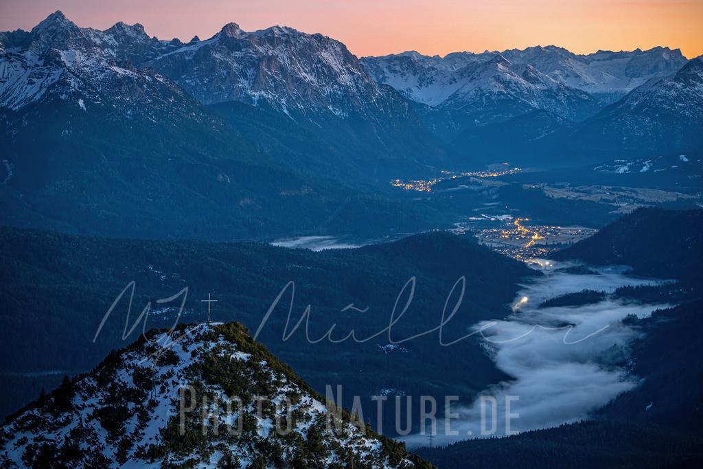 Gipfelkreuz zum Sonnenuntergang | Der Blick schweift vom Gipfelkreuz über die Nebelschwaden im Tal zu der Bergkette im Hintergrund