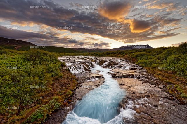 Wasserfall in wilder Landschaft nach Sonnenuntergang | Großer Wasserfall in einer weiten Landschaft bei Abendlicht, Wolken werden farbig angestrahlt, Wasserbewegung in Langzeitbelichtung - Location: Island, Golden circle, Bruarfoss