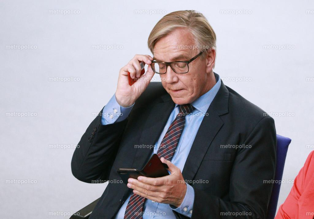 Dietmar Bartsch mit Abstimmungskarte und Smartphone im Bundestag