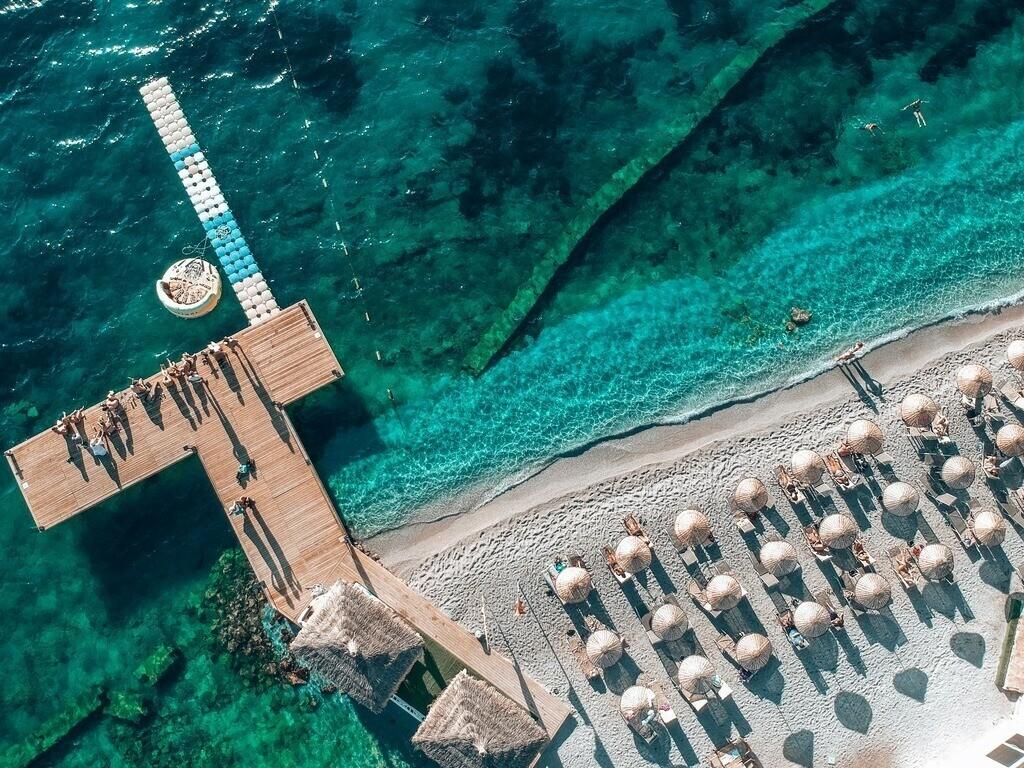 Drohnenperspektive am Strand von Bodrum   Blick auf den Steg und ein paar Sonnenschirme von oben
