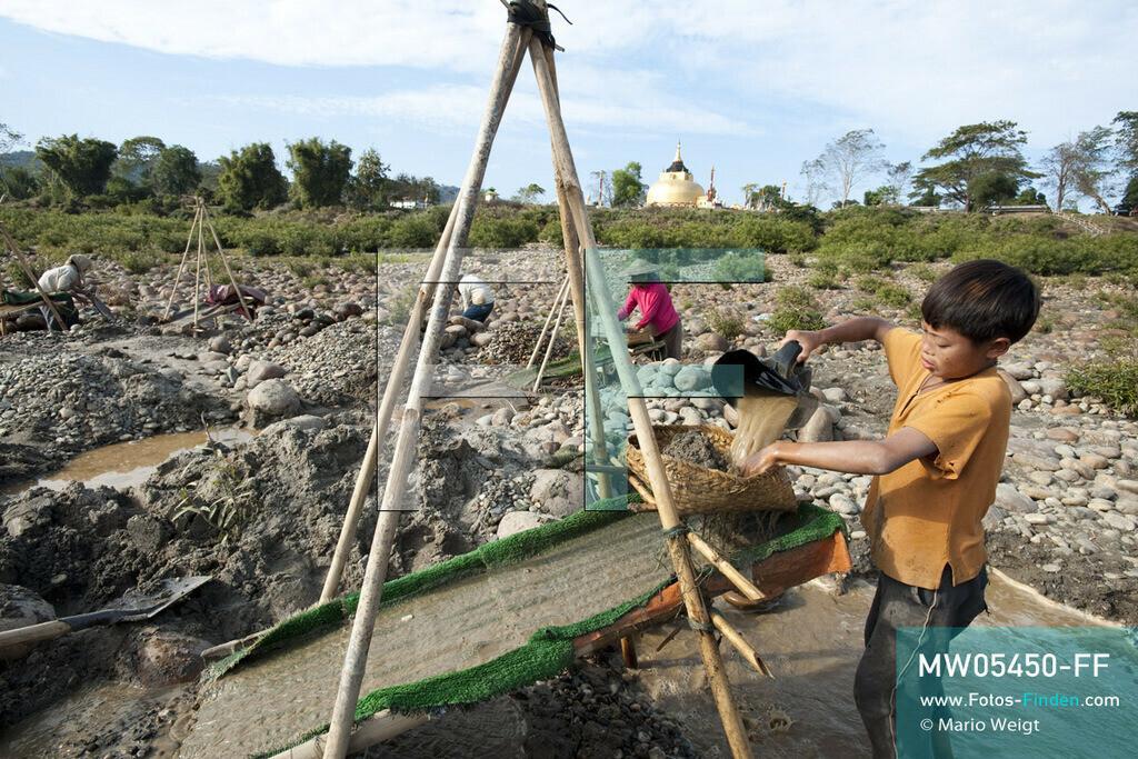 MW05450-FF | Myanmar | Kachin State | Myitson | Adee spült den Flusssand über die Holzrutsche und hofft, dass winzige Goldpartikel in der grünen Matte zurückbleiben. Der 13-jährige Maung Adee lebt mit seiner Tante und seinem Onkel im Dorf Thanphe, drei Kilometer vom Zusammenfluss des Ayeyarwady. Dort schürft Adee mit seiner Familie nach Gold.  ** Feindaten bitte anfragen bei Mario Weigt Photography, info@asia-stories.com **