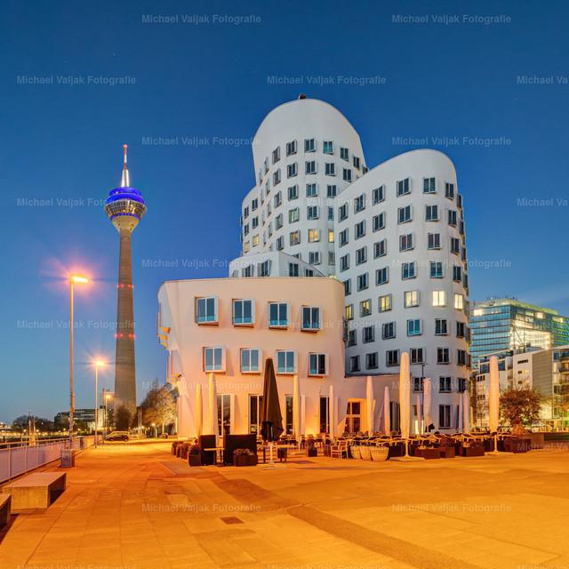 Im Medienhafen Düsseldorf (quadratische Version)   Blick zu einem der drei Gehrybauten am Neuen Zollhof im Düsseldorfer Medienhafen und dem Rheinturm im Hintergrund. Nach Einbruch der Dämmerung wird der Platz in ein orangenes Licht getaucht.