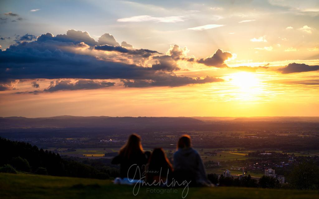 Sundowner am Samerberg | Drei Personen im Vordergrund beim Sonnenuntergang