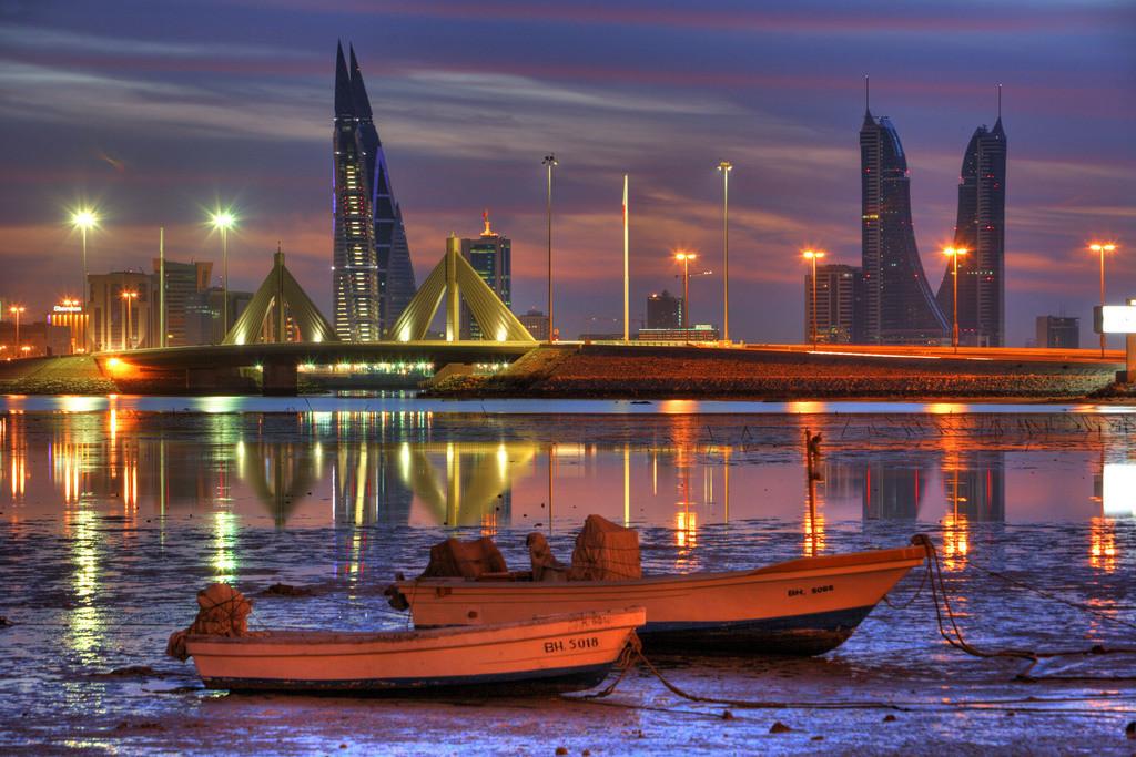 Bahrain | Skyline von der Conriche am King Faisal Highway gesehen, Muharraq Seite. World Trade Center Gebäude, links, danaeben die Türme des Financial Harbour Komplex. Abendliche Spaziergänger an der Corniche. Hauptstadt Manama, Königreich Bahrain. Persischer Golf.