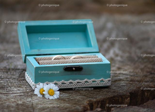 Ringkästchen mit goldenen Eheringen | ein blaues Ringkästchen mit zwei goldenen Eheringen und zwei Gänseblümchen steht auf einer hölzernen Unterlage bei Tageslicht