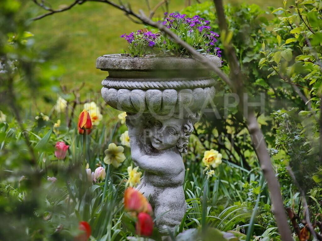 Blumenträger | Die Skulptur eines Blumenträgers im Garten während des Frühlingserwachens.