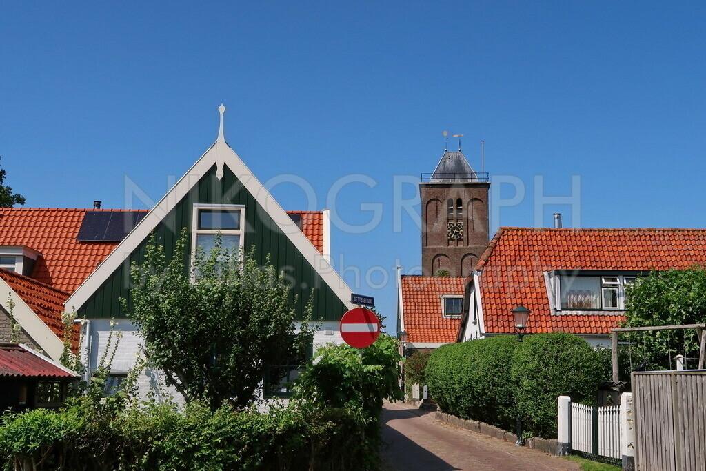 Oosterend | Straßensicht des Dorfes Oosterend im Osten der Insel Texel. Der Kirchturm ragt über die Häuser des Dorfes.
