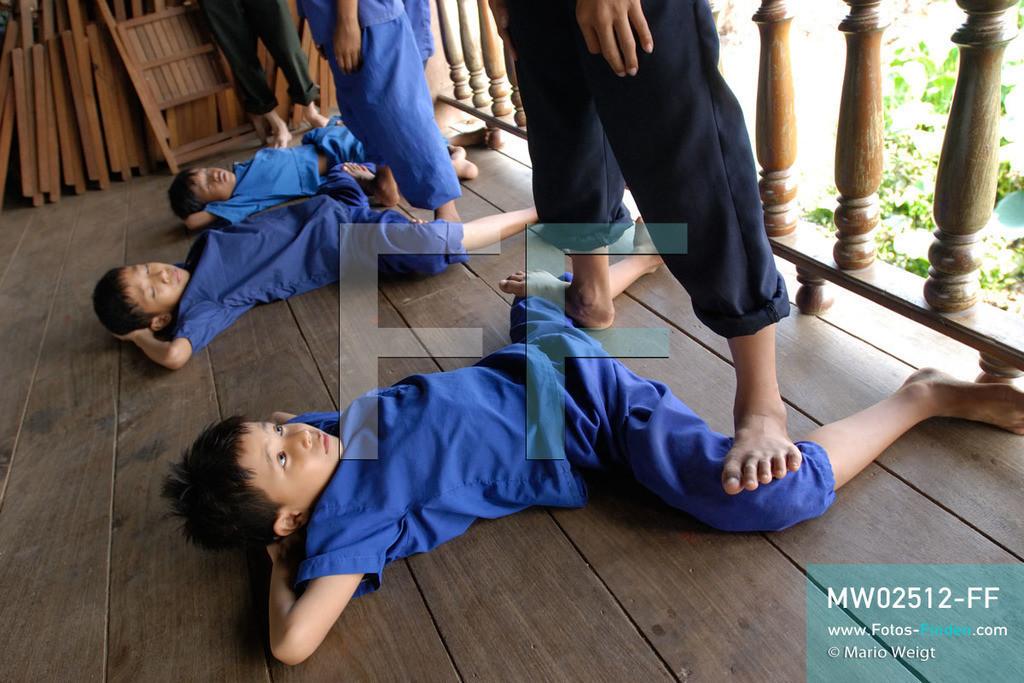 MW02512-FF | Kambodscha | Phnom Penh | Reportage: Apsara-Tanz | Schüler beginnen die Tanzstunde mit Dehnübungen. Sie lernen den Apsara-Tanz in einer Tanzschule. Sechs Jahre dauert es mindestens, bis der klassische Apsara-Tanz perfekt beherrscht wird. Kambodschas wichtigstes Kulturgut ist der Apsara-Tanz. Im 12. Jahrhundert gerieten schon die Gottkönige beim Tanz der Himmelsnymphen ins Schwärmen. In zahlreichen Steinreliefs wurden die Apsara-Tänzerinnen in der Tempelanlage Angkor Wat verewigt.   ** Feindaten bitte anfragen bei Mario Weigt Photography, info@asia-stories.com **