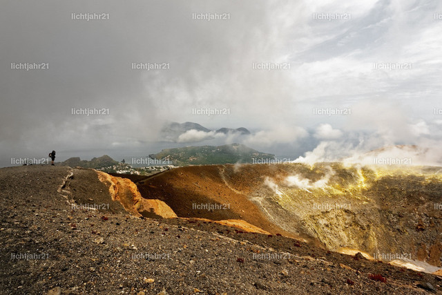 Blick vom Kraterrand über die Liparischen Inseln | Weiter Blick vom Kraterrand über die Liparischen Inseln im Mittelmeer, dramatische Wolken und Schwefeldämpfe, Person als Größenmaßstab - Location: Italien, Liparische Inseln, Vulcano
