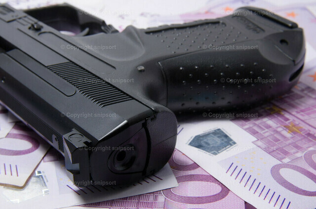 Pistole über 500-Euro-Scheinen