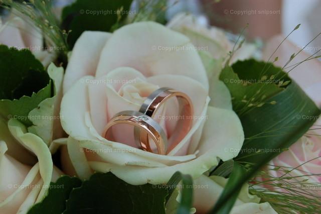 Zwei Eheringe | Zwei Eheringe in einem Blumengesteck für die Hochzeit