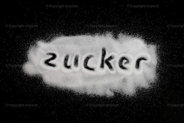 Konzept Zucker | In einen auf dem schwarzen Hintergrund verstreuten Haufen handgeschriebenes Wort
