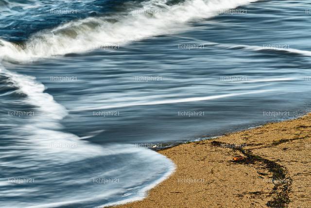 Dünung in Detailansicht | Detailansicht einer Welle, die an einem Sandstrand ausläuft, die blaue Farbe des Himmel spiegelt sich im flachen Wasser, etwas angespültes Seegras auf dem Sand, Schwarzweissbild, Wasserbewegung in dezenter Langzeitbelichtung - Location: Karibik, Kleine Antillen, Insel Guadeloupe