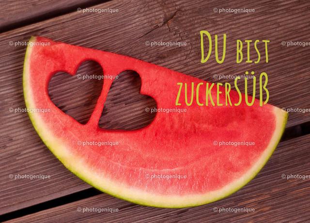 Postkarte Du bist zuckersüß   Postkarte Eine Scheibe einer roten Wassermelone mit zwei ausgestochenen Herzen und dem Text Du bist zuckersüß