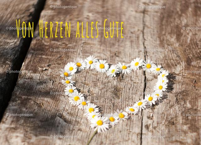 Postkarte Grußkarte Gänseblümchen von Herzen alles Gute | Postkarte Grußkarte Geburtstagskarte mit einem Herz aus den Gänseblümchen auf einem Holz-Untergrund bei Tageslicht mit dem Spruch Von Herzen alles Gute