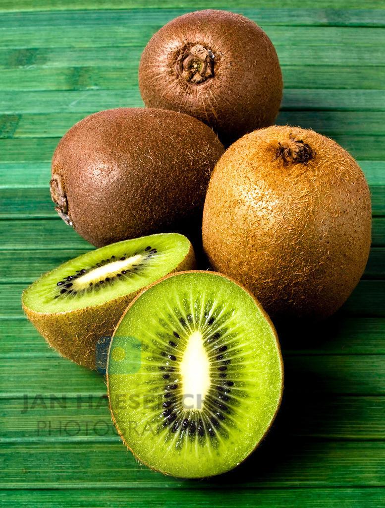 Kiwi | KIWI Frucht.  Der Name Kiwi für diese Frucht wurde aus marktstrategischen Überlegungen in Neuseeland erfunden und leitet sich vom Kiwi-Vogel ab.  Kiwis enthalten je 100 g Frucht etwa 71 mg Vitamin C. Sie enthalten außerdem das eiweißspaltende Enzym Actinidin, das jedoch beim Kochen zerstört wird. Rohe Kiwis vertragen sich daher nicht mit Milchprodukten – die Speise wird nach wenigen Minuten bitter, wenn die Früchte roh hinzugefügt werden, weil das Enzym in der Frucht das Milcheiweiß zersetzt. (Dabei bilden sich bitter schmeckende Peptide, die sonst nur beim bakteriellen Verderb auftreten.) Abhilfe schafft kurzes Dünsten mit etwas Zucker und Wasser oder Saft. Andererseits sind rohe Kiwis ein guter Nachtisch für eiweißreiche Speisen, da das Enzym die Verdauung der Eiweiße erleichtert. (Quelle: Wikipedia) ***© JHP / MEDIA - Jan Haeselich. Abdruck nur gegen Honorar / Kto. Jan Haeselich Nr. 1203128572 bei der Hamburger Sparkasse  BLZ 20050550  USTId.Nr.: DE189890741  7% Ust. Bitte beachten Sie meine AGBs unter www.jhp-media.de