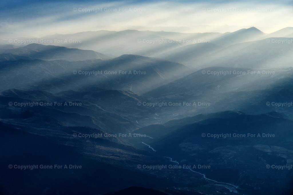 Albanien | Blick vom Mount Tomorr ins Tal. Sonnenstrahlen brechen durch die Wolken.
