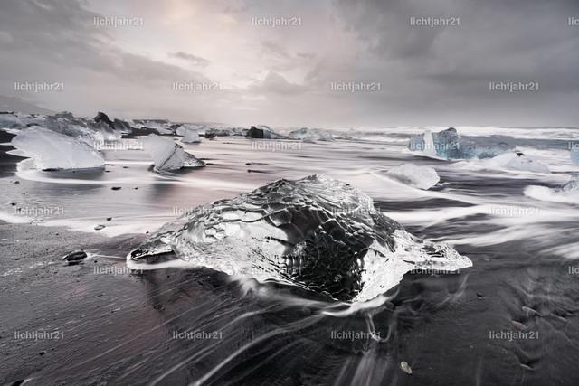 Eisblock am schwarzen Strand | Markanter Eisblock an einem schwarzen Strand mit starker Brandung, Bewegungsspuren des abfließenden Wassers auf dem dunklen Sand, im Hintergrund weitere Eisblöcke, Wellen rollen heran, kontrastreicher Himmel mit Wolken und etwas Farbe - Location: Island, Jökulsarlon (Jökulsárlón)