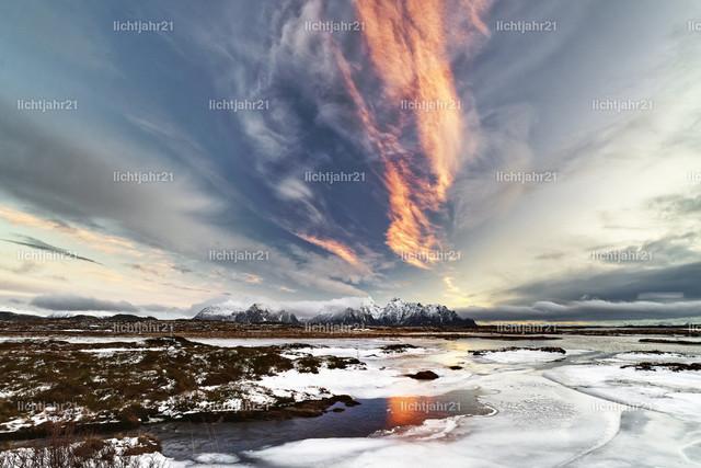 Eislandschaft | Eislandschaft mit Bergen im Hintergrund und einer rot gefärbten Wolkenformation, die sich im Wasser spiegelt - Location: Norwegen, Lofoten