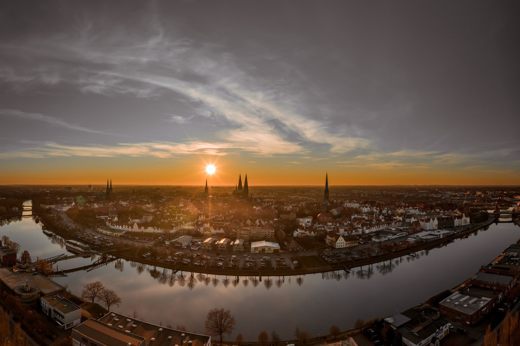 Golden Sunset - Hansestadt Lübeck im Sonnenuntergang  3:2 | Je nach Tageszeit und Wetterlage entstehen verschiedene Lichtstimmungen. Dieses Mal tauchte die Sonne kurz vor ihrem Untergang die Lübecker Altstadtinsel in ein herrliches, warmes Licht.  Die Bäume entlang des Kanals spiegeln sich im ruhigen Wasser. Eine besondere wohlige Stimmung breitet sich aus.  Dieses Bild kann mit seinen warmen Farbtönen das besondere Highlight an der Wand sein und wir so manchen Betrachter in seinen Bann ziehen.