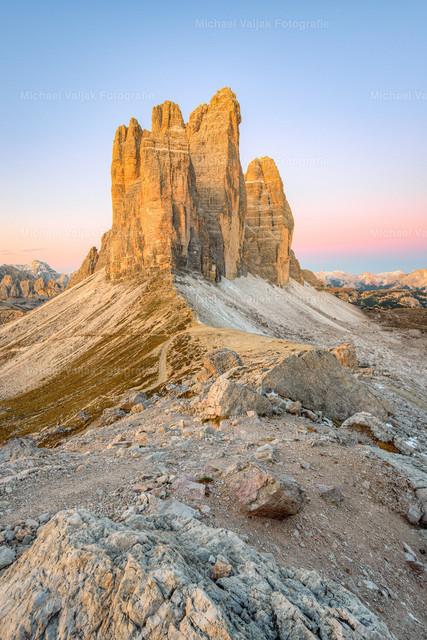 Drei Zinnen und Paternsattel in Südtirol | Blick über den Paternsattel zur Nordostseite der Drei Zinnen. Noch vor Sonnenaufgang setzt die Morgendämmerung die Felsen bereits in ein orangefarbenes Licht.