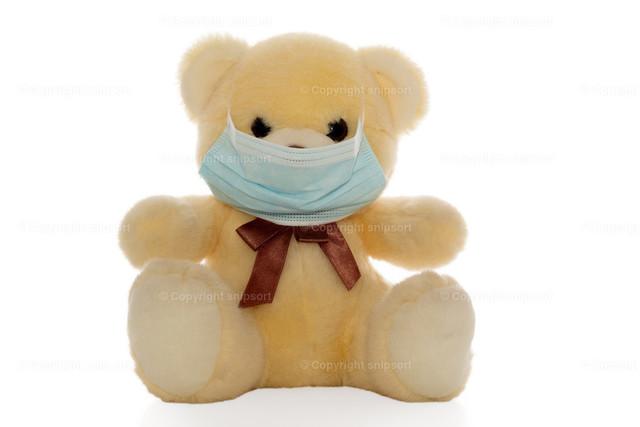 Plüschbär mit Maske | Ein flauschiger Plüschbär mit Mundschutzmaske als Konzept für Covid-19-Pandemie (freigestellt).