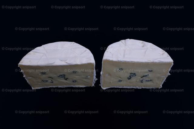 Blauschimmelkäse | Zwei Stück Blauschimmelkäse in zwei Hälften aufgeschnitten über schwarzem Hintergrund
