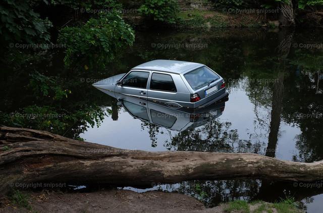 Auto im Fluss | Bei einem Autounfall von der Straße abgekommenes und im Fluss gelandetes Auto.