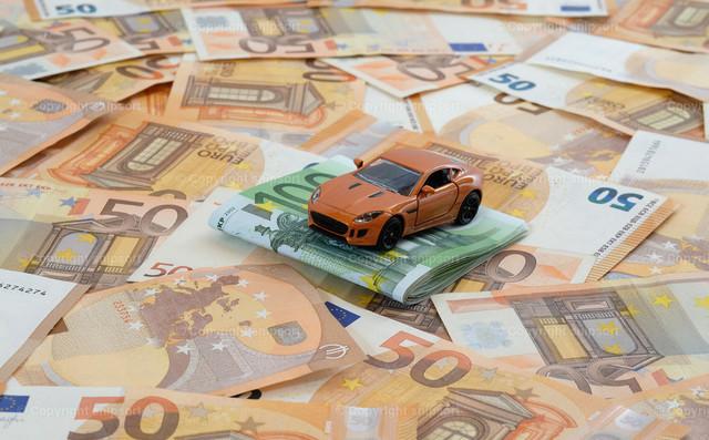 Orangenfarbenes Sportauto auf einem Geldstapel | Ein Modellauto auf flächendeckend ausgelegten 50-Euro-Banknoten mit 100-Euro-Banknoten zum Thema Konzept Autokosten