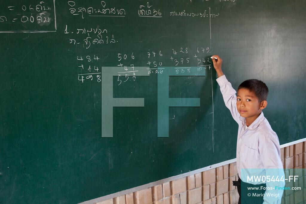 MW05444-FF | Laos | Provinz Sayaboury | Vieng Keo | Reportage: Pey Wan im Elefantendorf | Pey Wan während der Mathematikstunde. Er besucht die 3. Klasse.  Der achtjährige Pey Wan lebt im Elefantendorf Vieng Keo im Nordwesten von Laos. Im Dorf wohnen ca. 500 Leute mit 17 Arbeitselefanten. Sein Vater Hom Peng hat einen 31 Jahre alten Elefantenbullen namens Boun Van, mit dem er im Holzfällercamp im Dschungel arbeitet. Zum Elefantenfest schmückt Pey Wan den Jumbo und darf mit ihm an der Prozession durchs Dorf teilnehmen. Pey Wan möchte, wie sein Vater, später auch Elefantenführer werden.  ** Feindaten bitte anfragen bei Mario Weigt Photography, info@asia-stories.com **