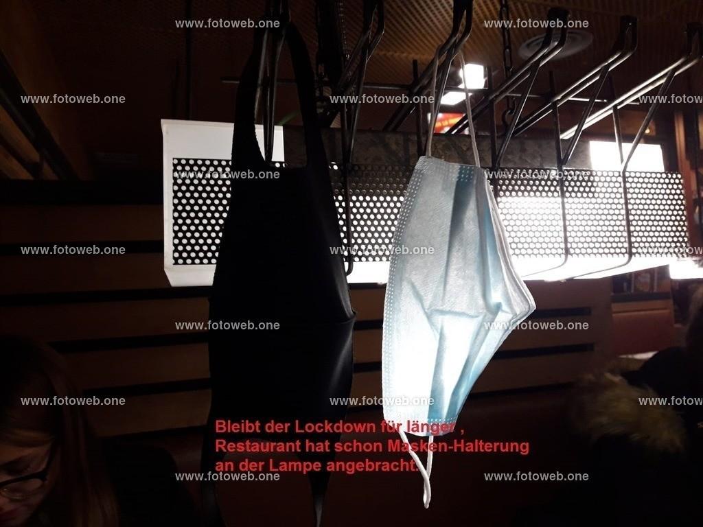 Bleibt der Lockdown für länger _ Restaurant hat schon Masken-Halterung an der Lampe angebracht. | Bleibt der Lockdown für länger , Restaurant hat schon Masken-Halterung an der Lampe angebracht.