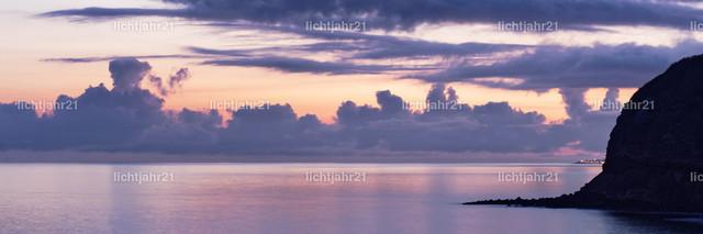 Abendlicht auf den Azoren | Farbiger Himmel mit unterschiedlichen markanten und kontrastreichen Wolkenformationen kurz nach Sonnenuntergang, Blick über Wasser mit Wolkenspiegelung, Bergsilhouette am Bildrand - Location: Azoren, Sao Miguel