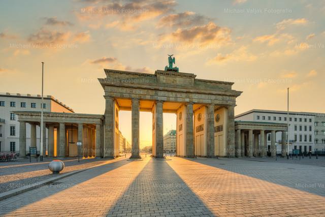 Brandenburger Tor   Sonnenaufgang am Brandenburger Tor, warm angeleuchtet von der gerade aufgegangenen Sonne. Die Säulen brechen das flach einfallende Sonnenlicht und führen mit den langen Schatten zu einem sehr schönen Lichteffekt auf den Pflastersteinen am Platz des 18. März.