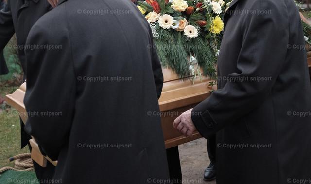 Beerdigung | Sargträger tragen einen mit Blumen geschmückten Sarg