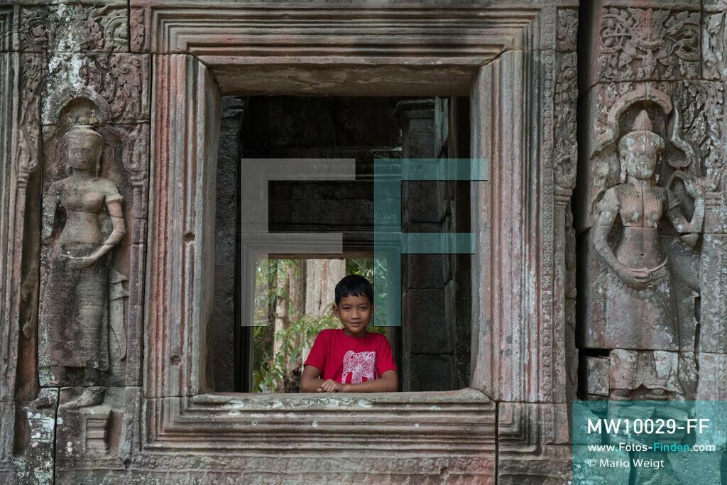 MW10029-FF | Kambodscha | Siem Reap | Reportage: Sombath erkundet Angkor | Sombath im Tempel Banteay Kdei.  Der achtjährige Sombath lebt in Kambodscha im Dorf Anjan, sechs Kilometer westlich von Siem Reap entfernt. In seiner Freizeit nimmt ihn manchmal sein Onkel in die berühmte Tempelanlage von Angkor mit. Besonders mag er die riesigen Wurzeln der Kapokbäume, die auf den alten Mauern wachsen. Seine Lieblingstempel in Angkor sind Ta Prohm, Banteay Kdei und Preah Khan.  ** Feindaten bitte anfragen bei Mario Weigt Photography, info@asia-stories.com **