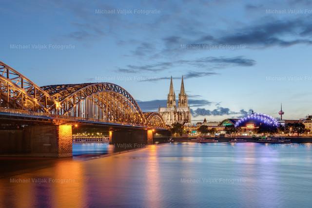 Köln am Abend | Blick auf die Skyline von Köln am frühen Abend mit der beleuchteten Hohenzollernbrücke, dem Kölner Dom, Musicaldome und im Hintergrund dem Kölner Fernsehturm.