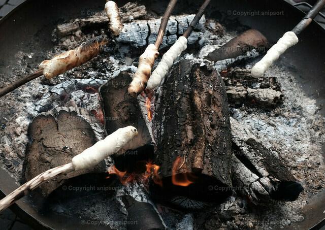Stockbrotspieße über dem Feuer | Aufgespießtes Stockbrot über glühender Kohle.