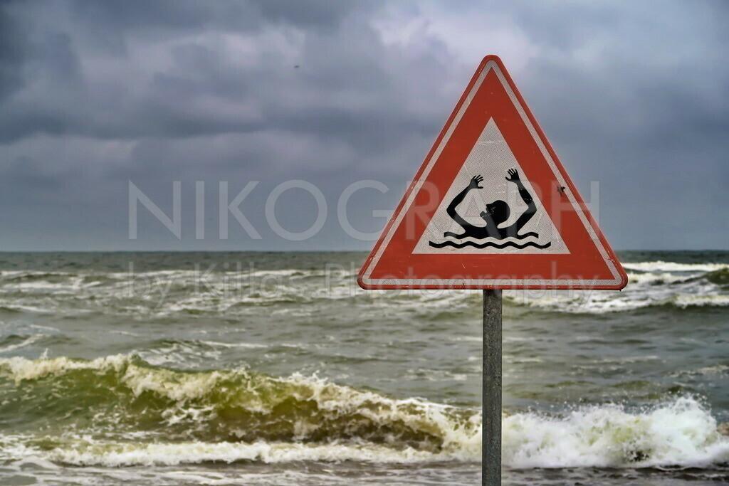 Warnschild am Strand | Ein Warnschild am Strand der Nordseeinsel Texel warnt vor den Gefahren der Strömung. Im Hintergrund sind die Wellen des aufgewühlten Meeres zu sehen.