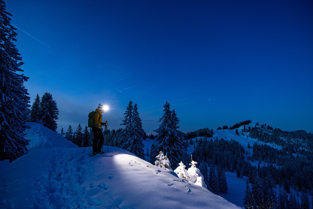 Snow shoe hike   Woman with headlamp in the night on her way with snow shoes.