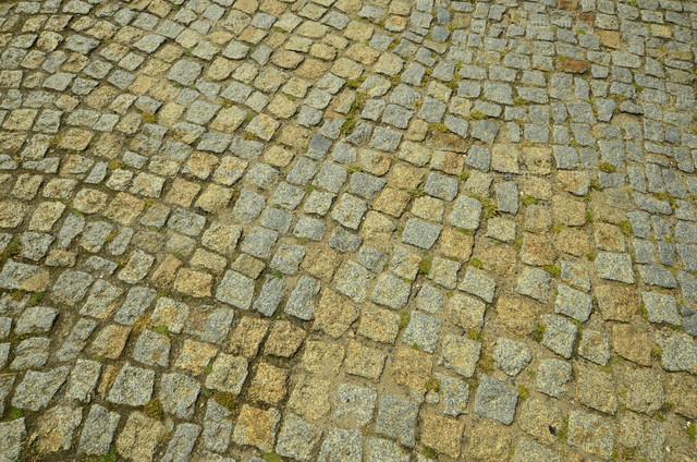 Kopfsteinpflaster | Detail von einem mit Pflastersteinen ausgelegten Gehweg.