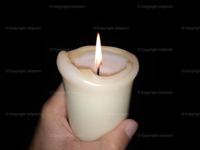 Kerze in der Dunkelheit | Eine männliche Hand mit einem brennenden Kerzenstummel in der Dunkelheit.