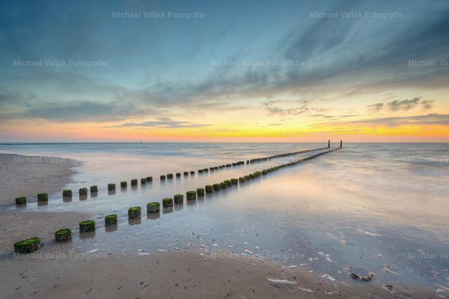 Abends am Strand von Domburg | Langzeitbelichtung weit nach Sonnenuntergang am Strand von Domburg in Zeeland in den südwestlichen Niederlanden. Zahlreiche Buhnen ragen hier ins Meer um die Wellen zu brechen. Aufgenommen während der Flut, kurze Zeit später waren die Holzpfeiler bereits vom Wasser bedeckt.