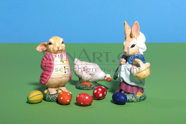 Ein dicker Osterhase und seine Frau mit einer Gans zwischen bunten Eiern | Ein dicker Osterhase im Frack und seine Frau im Kleid mit einem Korb, stehen mit einer weißen Gans zwischen bunten Ostereiern.