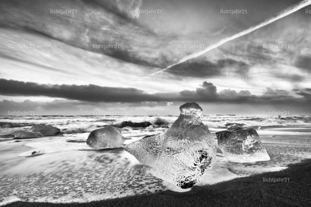 Eisblöcke am schwarzen Strand | Eisblöcke in blauen und dunklen Farbtönen an einem schwarzen Strand mit starker Brandung, das Eis spiegelt sich im nassen Sand, im Hintergrund rollen Wellen heran, Schwarzweißbild - Location: Island, Jökulsarlon (Jökulsárlón)