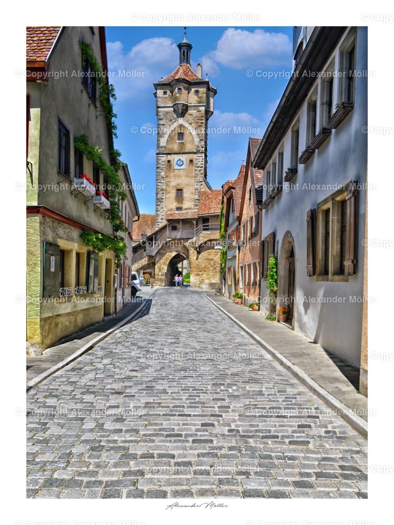 Rothenburg ob der Tauber No.51   Dieses Werk zeigt das Klingentor. Eine Besonderheit zeichnet das Klingentor aus: Es teilt sich eine Wand mit der Kirche St.-Wolfgang. Wehr- und Sakralbau sind auf diese einzigartige Weise miteinander verknüpft.