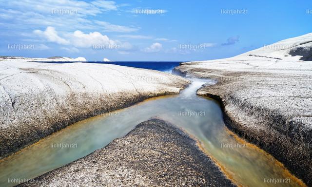 Zusammenfluss am Bimssteinstrand | An einem Strand aus weißem Bimsstein fließt Wasser aus zwei Gräben zusammen in's Meer, darüber ein blauer Himmel mit wenigen markanten Wolken - Location: Griechenland, Kykladen, Sarakiniko beach